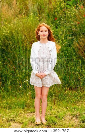 Outdoor portrait of a cute little girl of 8-9 years old with long red hair