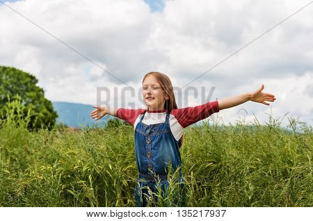 Little girl playing in green wheat field in summertime, wearing red and white t-shirt and overalls, arms wide open