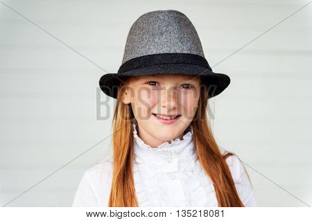 Close up portrait of pretty little girl of 8-9 years old against white wooden background. Kid girl wearing white vintage blouse and grey black hat