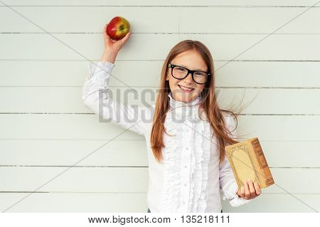 Happy little schoolgirl holding book and red apple, wearing white vintage blouse and black frame eyeglasses, standing against white wooden background. Back to school concept