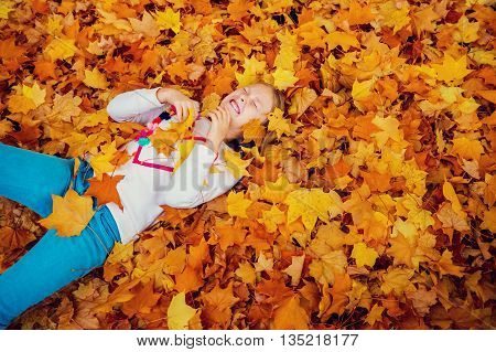 Autumn portrait of a cute little girl of 8-9 years old, playing with yellow leaves in the park