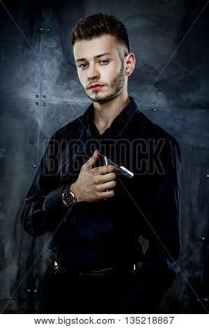 Elegant young handsome man. Studio fashion portrait.Portrait of a young brutal man with straight razor