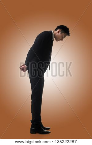 Asian business man looking down, full length portrait isolated