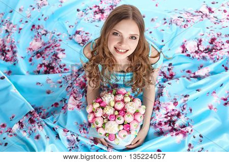 Young beautiful girl with a bright bouquet of paper flowers sitting on the floor, looking up and smiling.