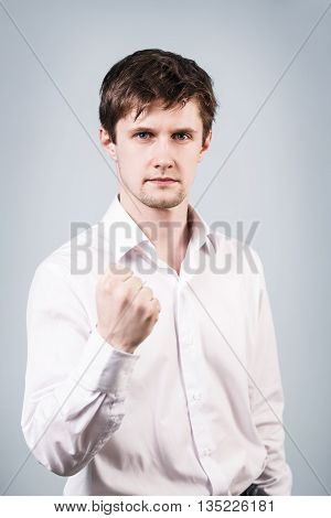 Young handsome businessman shows threaten fist on the gray background