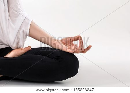 Closeup of woman's hands meditating in white room