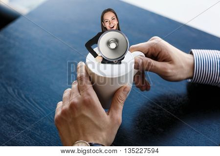 Young business woman shouting and sitting in cup of coffee