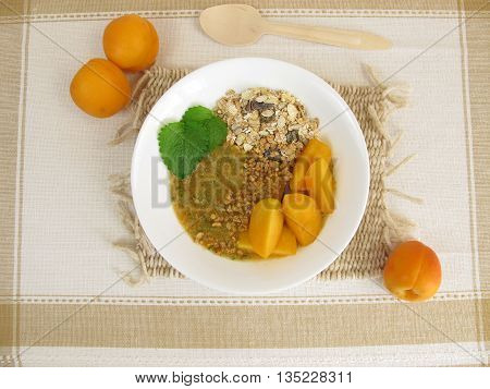 Smoothie bowl with muesli, apricot, lemon balm and almonds