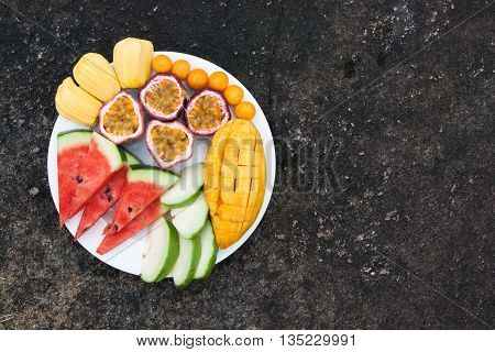 Assortment of sliced tropical fruits on plate. Background of dark stone.
