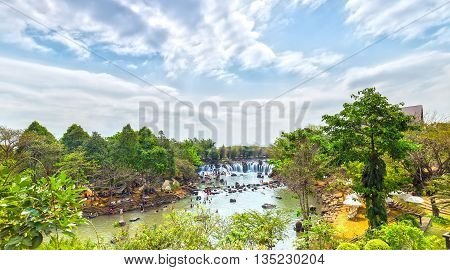Giang Dien Waterfall above with water pouring down billowing white, surrounded by a forest covered attract many tourists to the resort, above the beautiful cloudy sky sunny day fresh welcome freshness