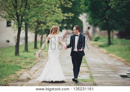 Beautiful couple of happy stylish newlyweds walking in the park on their wedding day with bouquet.