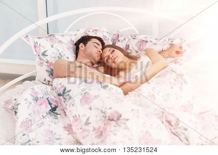 Portrait of beautiful couple laying on bed in room with blight sunlight