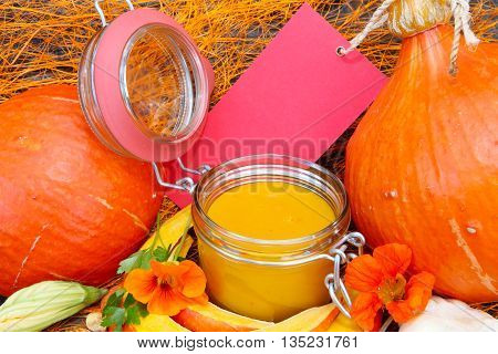 Two pumpkins with red shield and pumpkin soup in preserving jar