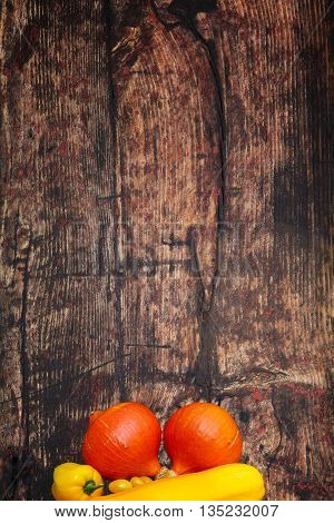 Two pumpkins with paprika and zucchini on old wood