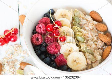 Healthy breakfast. Oatmeal porridge banana raspberries blueberries red currants pumpkin seeds and almonds in a bowl on white background. Closeup.