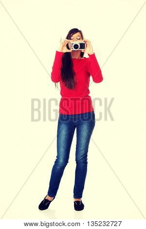 Woman taking a photo with a camera.
