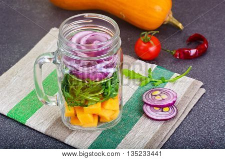 Salad with Pumpkin, Arugula and Red Onion in Glass Jar Studio Photo