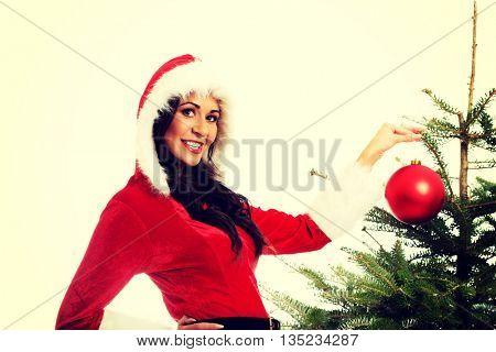 Smiling woman decorating christmas tree