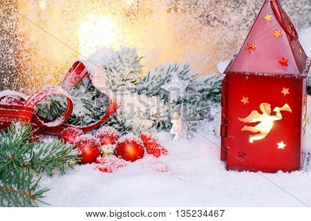 a red lantern with pine green and Christmas decoration on window