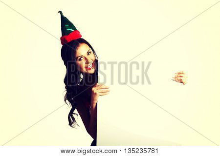 Woman wearing elf clothes holding banner