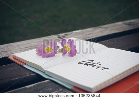 Alive text on open notebook with flower on wooden table