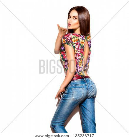 Fashion model brunette girl in sexy casual wear, jeans and bright top isolated over white background. Trendy dressed young woman. Shopping concept