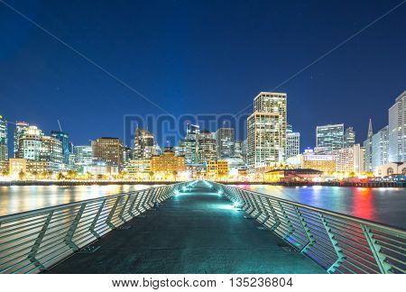 empty footpath to modern office buildings near water in san francisco at night
