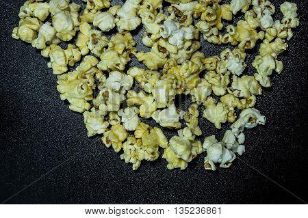 Caramel popcorn on dark background with hard light