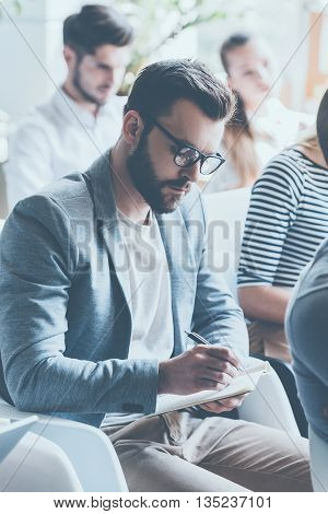 Making notes. Young handsome man making notes in his notebook while sitting on conference with other people