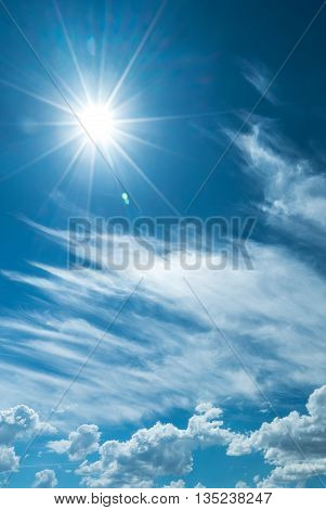 Vertical image of sky with clouds and shining sun