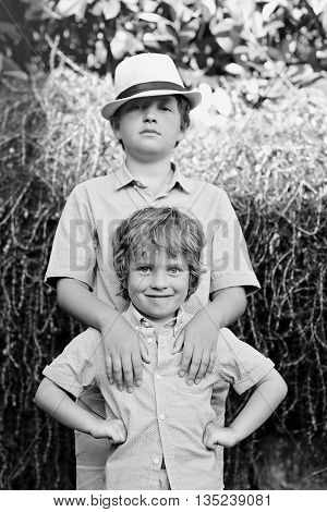 black and white portrait of a two brothers outdoors .