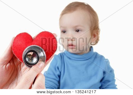 Concept of health and care. Baby and cardiologist heart symbol in hand and stethoscope.