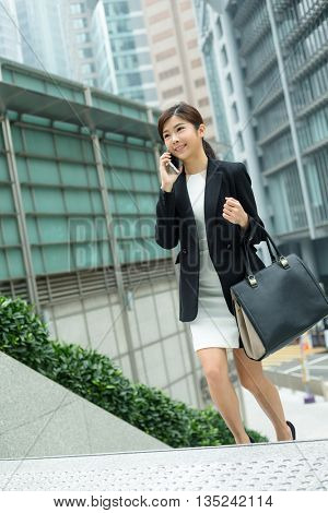 Young Businesswoman talk to mobile phone and walking on step