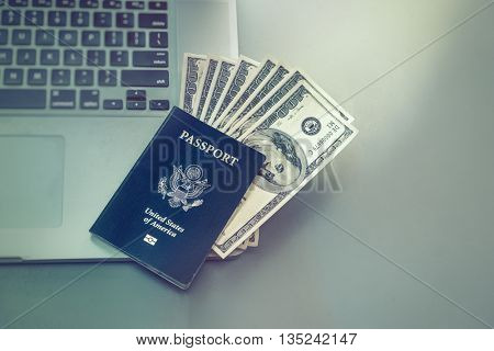 Booking travel option abroad online concept image.  Passport with American dollars onto of laptop computer.