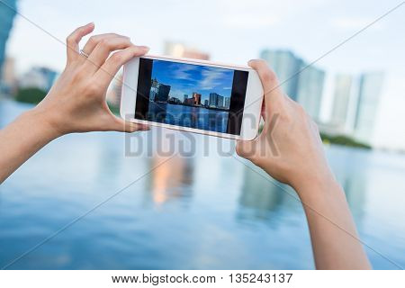 Hand taking photo on cellphone in Macau city