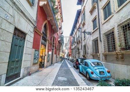 VERONA, ITALY - SEP 5, 2015: Little beautiful Italian street with shops and parked cars. Verona, Italy.