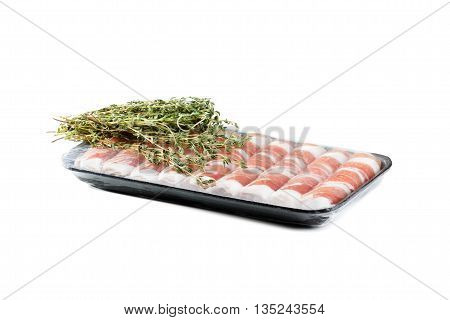 Slices of bacon roll closeup in disposable containers with herbs isolated on white background, cooking food