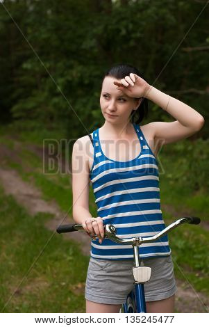 a young girl on her bike in the woods a tired brunette in striped t-shirt