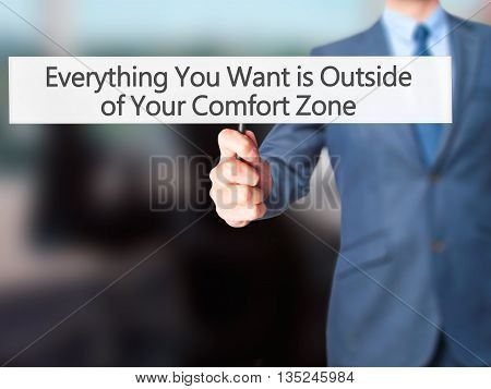 Everything You Want Is Outside Of Your Comfort Zone - Businessman Hand Holding Sign