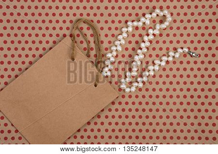 Handmade Shopping Bag Of Craft Paper, Gift Bags And Pearl Jewelry On Craft  Paper Background In Red