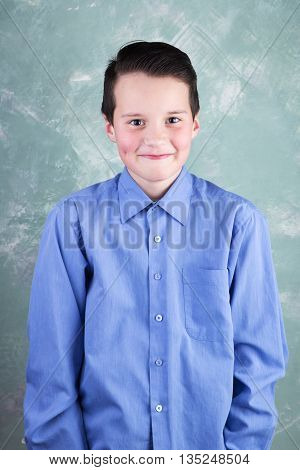 Portrait Of The Beautiful And Smile Schoolboy On Green Grange Background