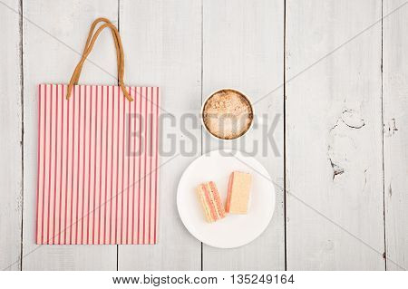 Meeting In A Cafe - A Cup Of Coffee, Waffles And Shopping Package On White Wooden Table
