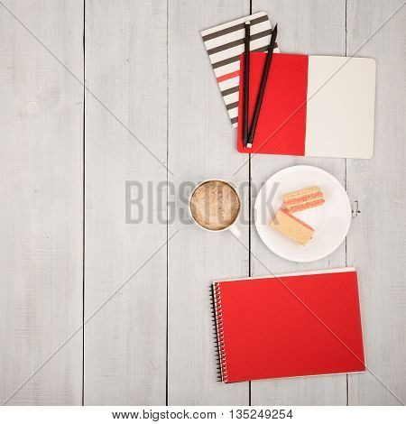 Office Table With Notepads, Cup Of Coffee And Waffles On White Wooden Desk
