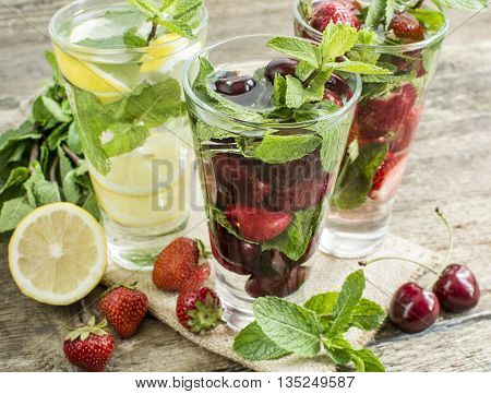 detox water with cherries strawberry lemon and mint in a glass on a background of leaves of mint and strawberries on a wooden table close-up