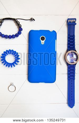 Smartphone in blue case with ring braslets with rhinestones scrunchy blue watch on white wooden background with copy space. Top view flat lay