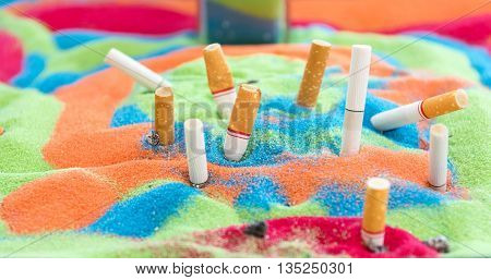 Smoked cigarettes in the sand beautiful colors  in the ashtray.