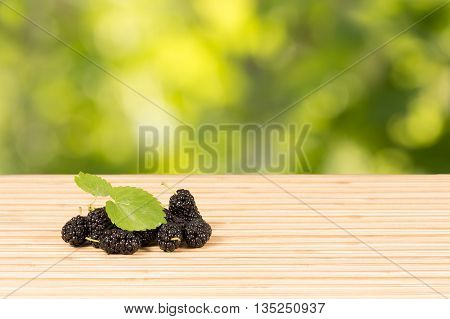Heap of ripe black mulberries with green leaves on table on green leaves background with option to insert your product . Horizontal composition