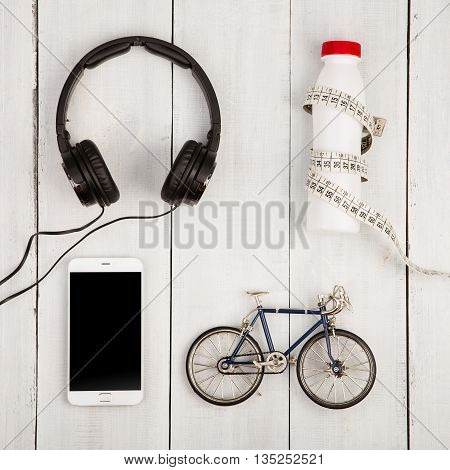 Travel And Sport Concept -  Bicycle Model, Headphones, Smartphone, Bottle Of Water And Centimeter Ta