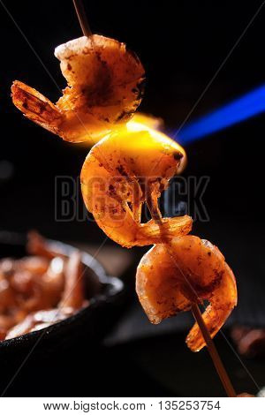 Three shrimp on a stick cooked blue gas, close-up