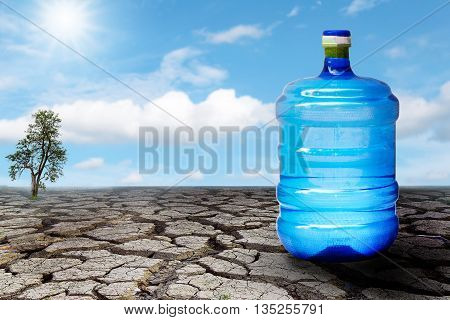 Large plastic water bottle on the ground, dry and cracked with blue sky background.